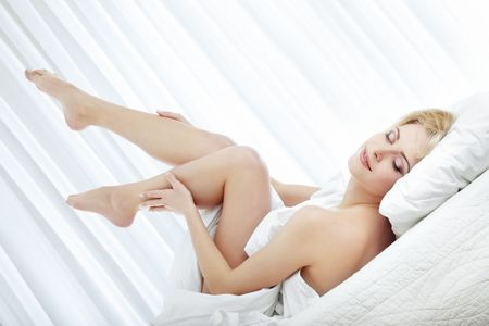 Elegant lady with legs laying on the bed at the morning Stock Photo - 4765900