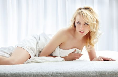 Sexy lady laying on the bed and covered by the blanket Stock Photo - 4821465