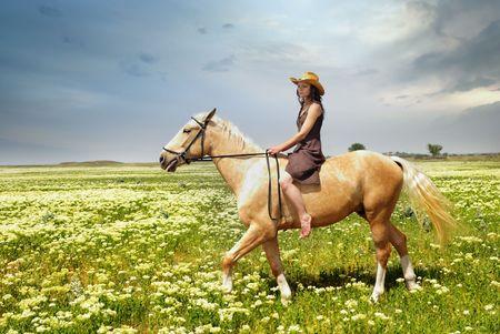 Mujer cabalgando sobre un caballo en el campo con hierba verde Foto de archivo - 4825638