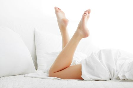bed clothes: Woman legs on the bed with white bed clothes