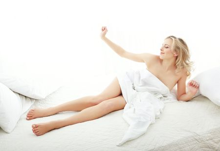 Awaking lady on the bed at the early morning photo