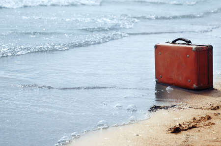 parting the sea: Lost orange handbag on the beach Stock Photo