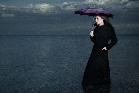 Lady with umbrella standing under the rain in the sea photo