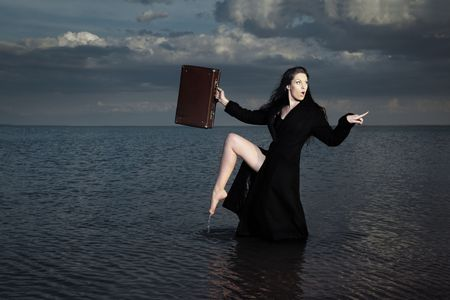 crazy woman: Stylish lady in the black coat with case standing in the dark water Stock Photo
