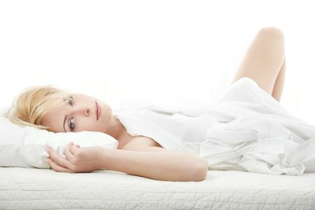 bedstead: Lady laying on the bed at the morning Stock Photo