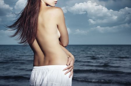 Lonely nude lady standing at the cloudy beach Stock Photo - 5212159