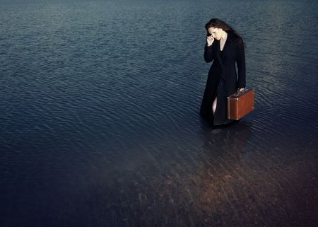 Sad alone woman with bag standing in the water Stock Photo - 5212178