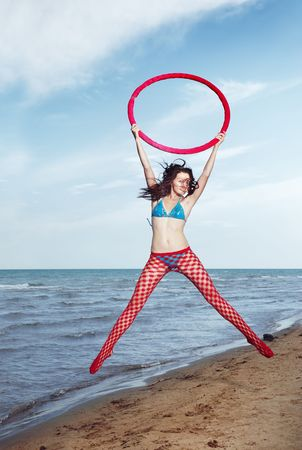 Smiling lady with red hoop jumping at the beach photo