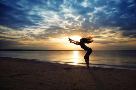 shadowgraph: Dancing dynamic woman at the beach during sunset