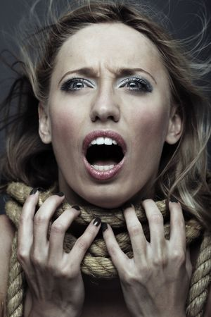 Screaming and suffering woman with terrible rope on her neck photo