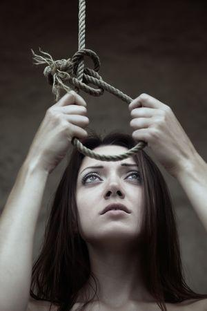 Sad lady holding the slipknot of the scaffold Stock Photo