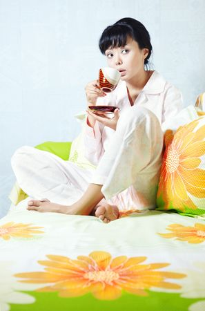 Lady sitting on the bed and drinking coffee photo