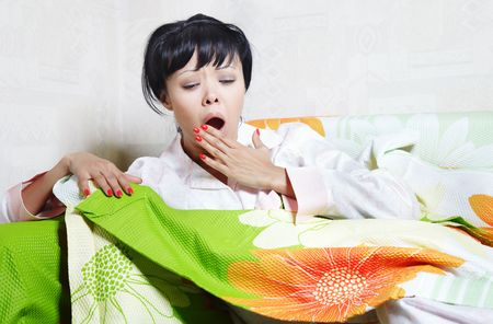 Yawning lady on the bed covered by colorful blanket photo