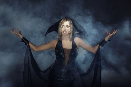 necromancer: Angry lady in witch costume conjuring in the smoke