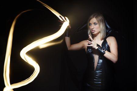 beldam: Magic light in studio and woman in witch costume. Long exposure