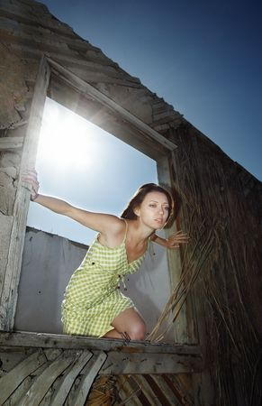 Lady trying to jump out the window of the old building Stock Photo - 5673687