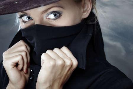 bandidas: Mujer con sombrero de espionaje con el rostro cubierto por el cuello de la chaqueta