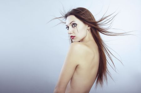 Naked sad lady with blown long hairs and Gothic makeup photo