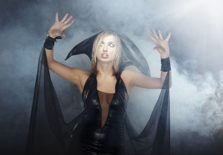 beldam: Indoors photo of the woman in witch costume in the heavy smoke