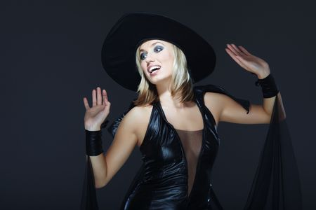 Smiling lady in the Halloween witch costume on a dark background Stock Photo - 5762231