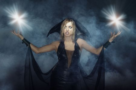necromancer: Woman in the Halloween witch costume in heavy smoke with magic flares and flashes Stock Photo