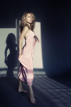 nifty: Elegant lady with curly hairs dancing indoors with shadow