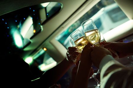 merriment:  the human hand holding wine glasses in limousine