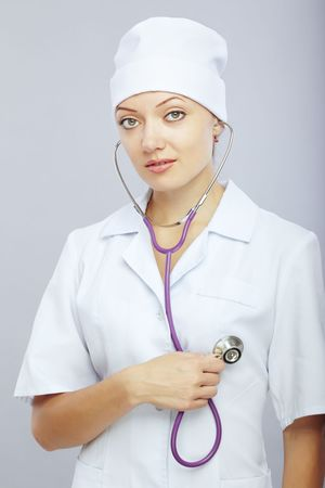 auscultoscope: Young female doctor with stethoscope monitoring her heart Stock Photo
