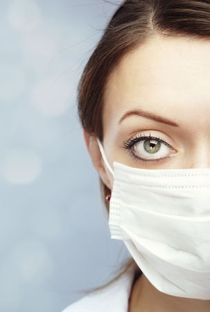 head protection: Female doctor on a blue blurred background in the face mask against flue infection Stock Photo