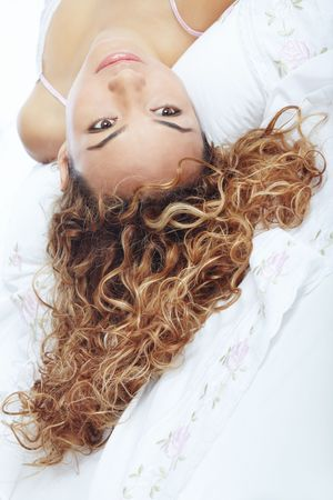 Sexy lady with curly hairs laying on the bed. Close-up portrait photo