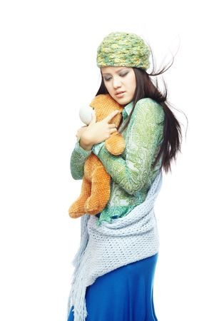 Sad young lady with blown hairs in the stylish clothes embracing Teddy bear on a white background  photo