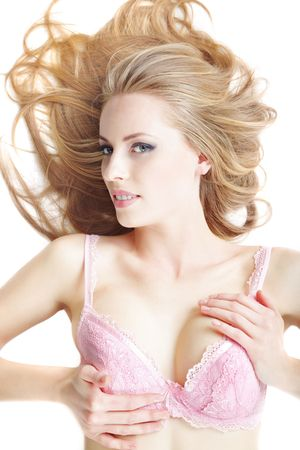 Sexy Caucasian lady with perfect makeup laying on a white background in pink brassiere Stock Photo - 6117928