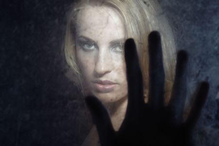 Portrait of the woman indoors behind the dirty glass and touching by the fingers photo