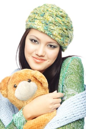 Smiling lady in the stylish winter clothes and cap holding Teddy bear on a white background photo