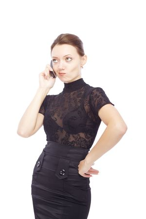 Dissatisfied businesswoman standing akimbo on a white background talking via cell phone photo