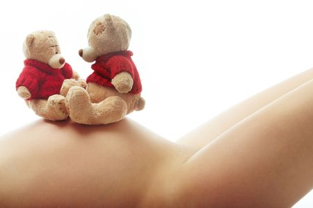 animal body part: Body of the laying pregnant woman and toys on her belly Stock Photo