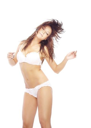 Young brunette lady in lingerie dancing on a white background  photo