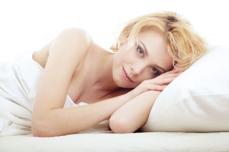 Elegant smiling lady in the bedroom laying on a white bed photo