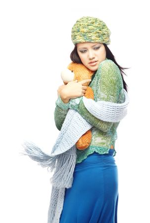 Young lady in the winter clothes embracing Teddy bear on a white background photo