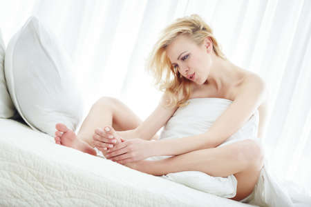 Elegant lady in the bedroom pampering her foot photo