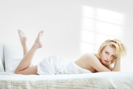 Young blond lady laying in a bedroom with window shadows on the wall photo