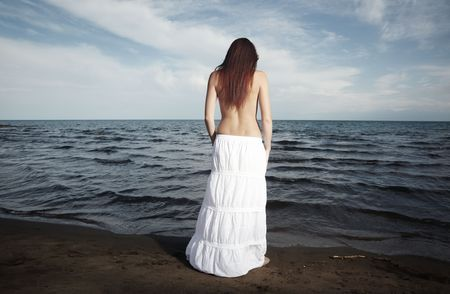 Rear view on the sad lady with long  hairs standing at the beach Stock Photo - 6471377