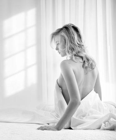 Photo noir et blanc de la jeune femme blonde dans une chambre à coucher avec fenêtre ombres sur le mur Banque d'images - 6527112