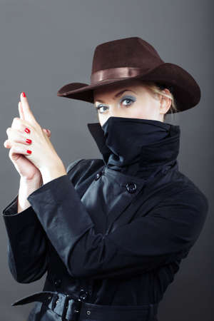 bandit:  gangster lady with cowboy hat on a gray background Stock Photo