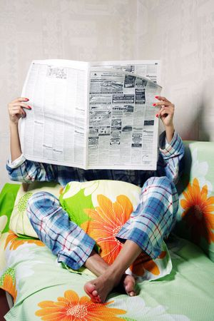 gazette: Unrecognizable woman indoors reading newspaper