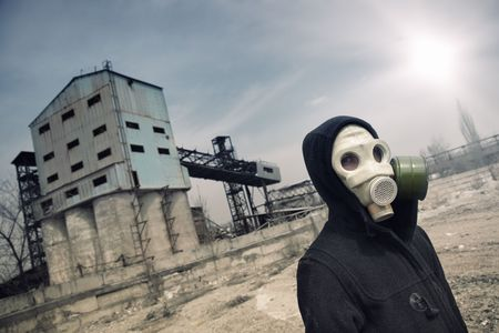 gaseous: Human in gas mask outdoors and industrial factory on a background