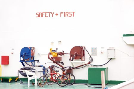 health facilities: Safety First inscription on the wall and two bikes parked near the pressure pump. Industrial site Stock Photo