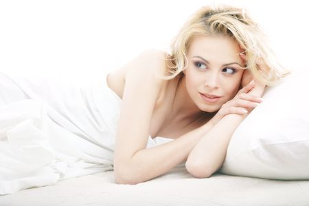 Sexy blond lady laying and relaxing in the bedroom on a white background photo