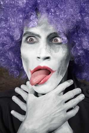 Crazy clown choking himself. Vertical photo. Artistic darkness and colors added photo