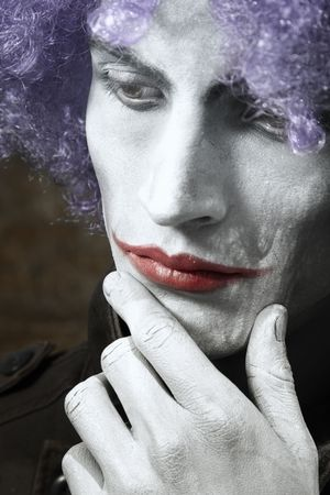 Single sad funny man with theatrical makeup and wig. Vertical photo with dramatic colors and toning photo